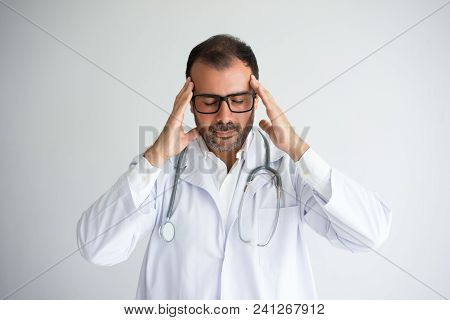 Portrait Of Frustrated Medical Worker Holding Head In Hands. Mid Adult Caucasian Male Doctor Wearing