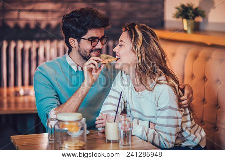 Beautiful Loving Couple Sitting In A Cafe Sharing Cookie. Love And Romance Concept.