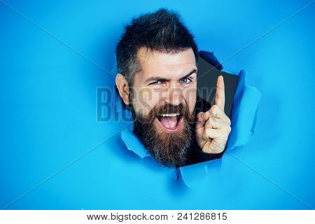 Bearded Man Making Hole In Paper. View Of Male Face Through Hole In Blue Paper. Bearded Man Looking