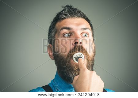 Light Bulb In His Mouth. Handsome Man In Denim Shirt With Light Bulb In Mouth. Man Trying To Eat Bul