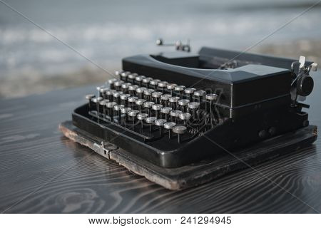 Black Typewriter On The Background Of The Sea At Dawn. Summer Beach
