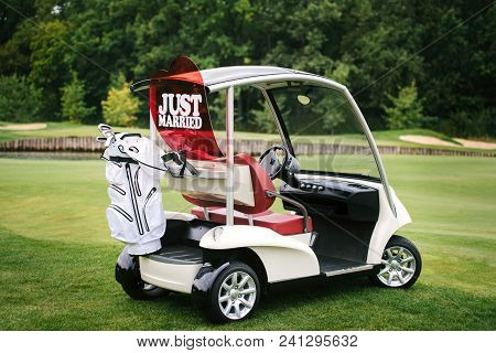 Golf Cart On Golf Course, Copy Space. Just Married Sign On Red Heart On Empty Golf Car Outdoors. Wed