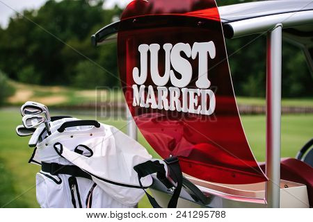 Just Married Sign On Red Heart On Empty Golf Cart Outdoors. Wedding Concept. Golf Car On Golf Course