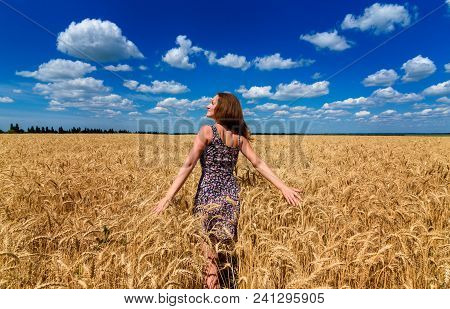 Beautiful Happy Young Woman In Golden Wheat Field With Cloudy Blue Sky Background, Copy Space. Girl