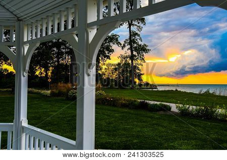 View Of The Sun Setting On The St Lawrence River In Trois-rivieres, Quebec From A Gazebo On The Bank