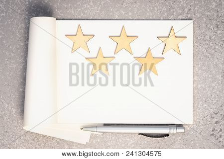 Paper Notebook, Five Wooden Stars And Pen Top View With Copy Space. Writing A 5 Stars Review Concept