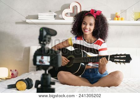 Happy Black Girl At Home Playing Guitar. Young African American Woman Working As Web Influencer, Rec