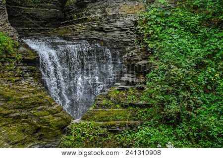 A Water Fall In The Watkins Glen State Park In New York With Vegetation On The Tiers Of Rock Formati