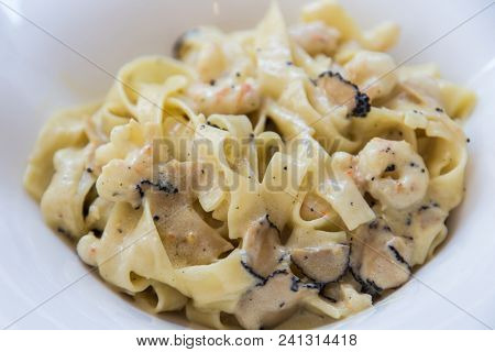 Plate of tagliatelle pasta with shaven truffles and shrimps in cream sauce