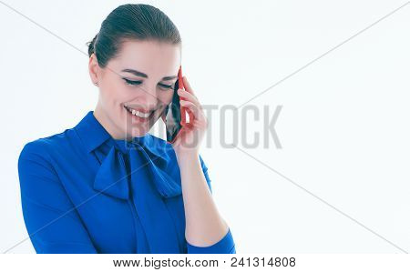 Pleased Smiling Real Estate Female Agent Talking On Mobile Phone. Busy Businesswoman Working On Whit