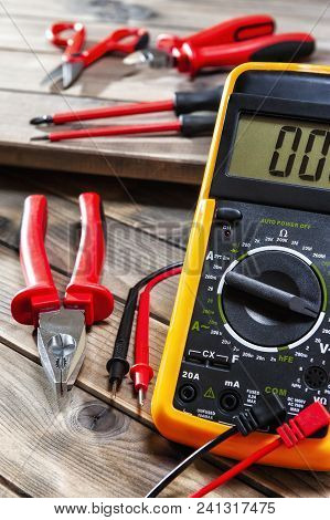 Close Up Of Work Tools On Electrical Installations, On An Antique Wooden Table.