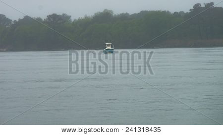A Fisherman Aboard A Boat In The Early Morning Fog Near The Delaware Seashore State Park.