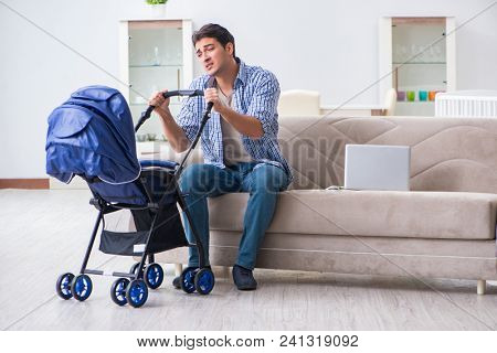 Young father looking after newborn baby at home
