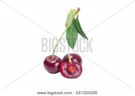 Red Cherry On A Branch With A Green Leaf, Cut In The Middle To The Bone, Isolated On A White Backgro