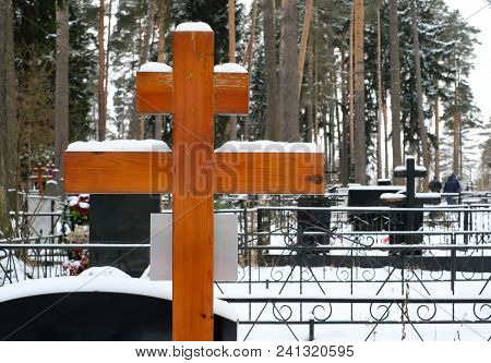 Wooden Cross And Artificial Flowers On The Grave Of An Orthodox Cemetery In The Winter
