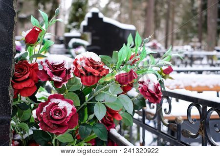 Artificial Flowers Bouquet Of Roses On The Grave In The Winter. Cemetery Decorations. Selective Focu