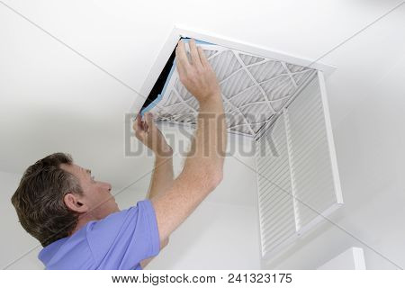 Guy Placing Into A Square Ceiling Intake Vent A Clean White And Blue Air Filter. As Regular Monthly