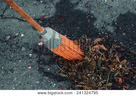 The Orange-colored Broom Of Which Is Cleaned In The Street With Rubbish And Foliage