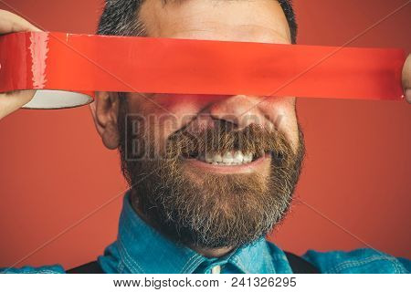 Closeup happy man with duct tape over eyes. Smiling bearded man wrapping insulating tape over his eyes. Businessman with happy face covered by red adhesive tape his eyes. Isolated on red background. poster