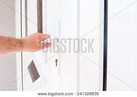 Front Door. Hand Holds Doorknob On Front Door Pvc