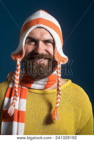 Smiling Handsome Bearded Man Wearing Winter Funny Hat And Scarf. Attractive Man With Beard And Musta