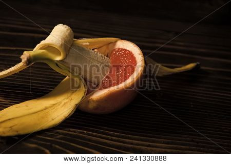 Banana With Yellow Peel In Red Grapefruit On Wooden Background, Sex And Sexual Intercourse, Fruit Lo