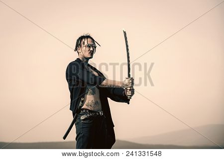 High Fashion Portrait Warrior With Dreadlocks And Open Clothes Showing Tattooed Torso. Man With Kata
