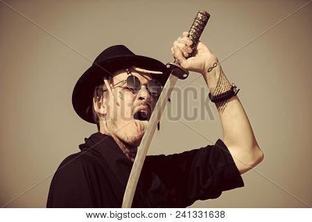 Man Looking At Camera. Martial Arts Concept. Man Licking Metal Blade Of Sword On Grey Sky. Defense,