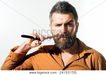 Hairdresser Demonstrating Sharp Blade Of Barbershop Accessory. Bearded Man Having Shave In Barbersho