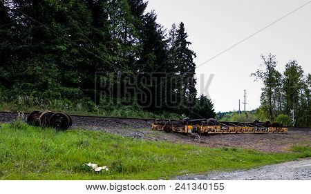 An Overturned Derailed Railroad Car Lying Next To The Tracks In Pieces