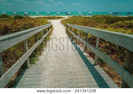 Dramatic View Of Wood Bridge Looking Toward A Sandy Ocean Beach With Colorful Umbrellas On A Sunny D