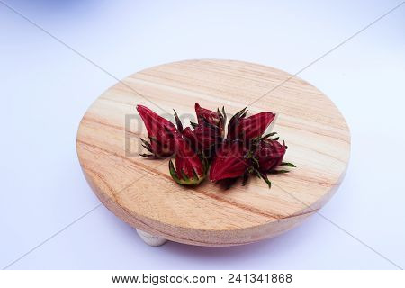 Rosella Or Hibiscus Or Kharkade Or Malvaceae Or Sorrel Seeds On Wood Round Cutting Board On White Ba