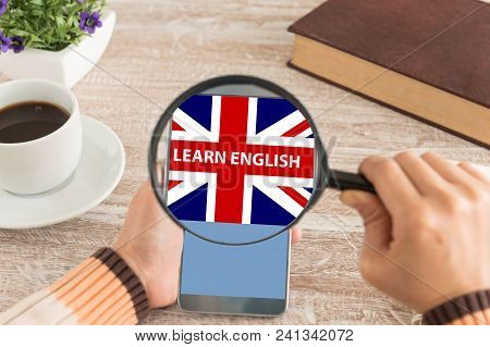 Learn English Concept. Women Hands Use The Magnifying Glass Screen Smart Phone To Learn English On T