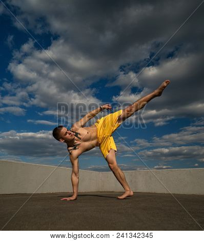 Tricking On Street. Martial Arts. Man Kick With Hand Support Barefoot. Shooted From Bottom Foreshort