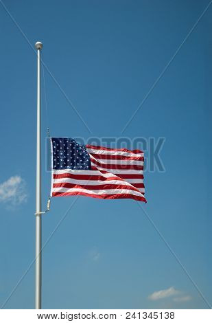 The United States Flag Flying At Half-mast Or Half-staff On A Flagpole. Blue Sky Background With Cop