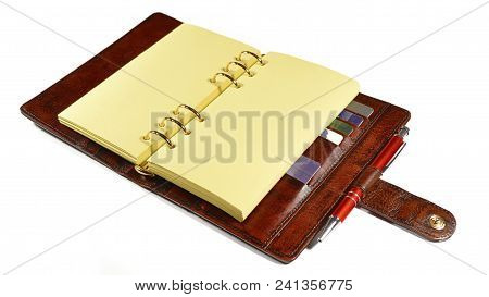 Business Organizer In Brown Leather With Blank Yellow Pages Laying On The Table