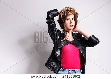 Portrait Of A Young Woman In A Black Leather Jacket And Pink T-shirt. Punk, Rock Style Fashion