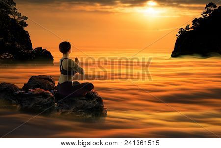Yoga Woman Meditating In Lotus Pose Sitting In Clouds During Beautiful Sundown