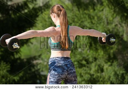 Fitness Woman With Dumbbells Against On Natural Background. Back View. Sport Concept