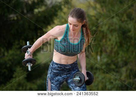 Sporty Girl With Two Dumbbells, One Dumbbell Holds On The Arm Bent For The Biceps Workout.