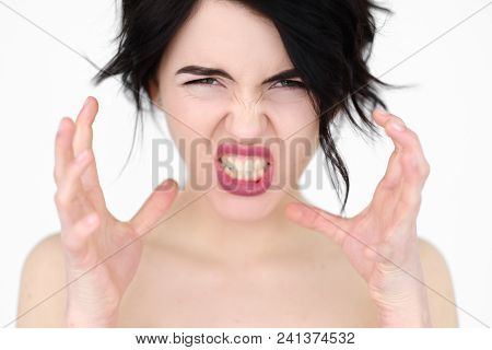 emotion face. enraged infuriated woman baring her teeth. female ready to kill or strangle with bare hands. young beautiful brunette girl portrait on white background. poster