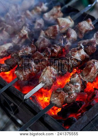 Shashlik Preparing On A Barbecue Grill Over Charcoal. Pieces Of Meat On Skewers. Shish Kebab Prepare