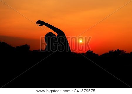 Silhouette Of Male Meditating And Yoga Practicing With Exercise At Sunrise In Public Park Morning