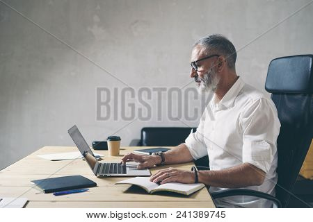 Positive Bearded Businessman Using Mobile Laptop Computer While Sitting At Wooden Table At Modern Co