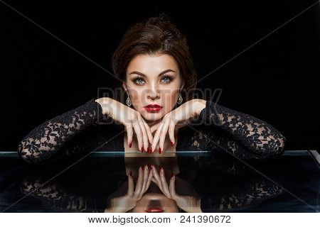Beautiful Young Woman With Red Lips And Fancy Hairstyle Wearing Black Dress. Studio Beauty Shot On B