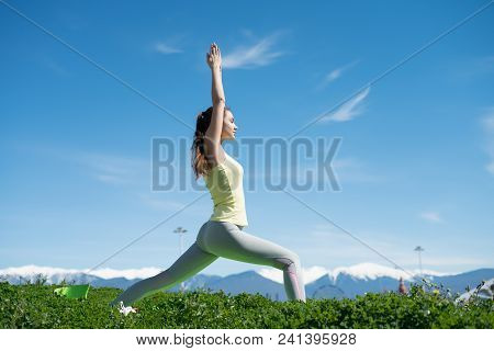 Slender Active Girl Engaged In Yoga On The Green Grass In The Park, Meditates And Relaxes