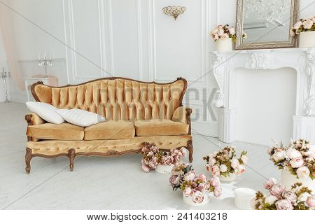 Beautiful Provance Living Room With Vintage Brown Sofa Near Fireplace With Flowers And Candles.