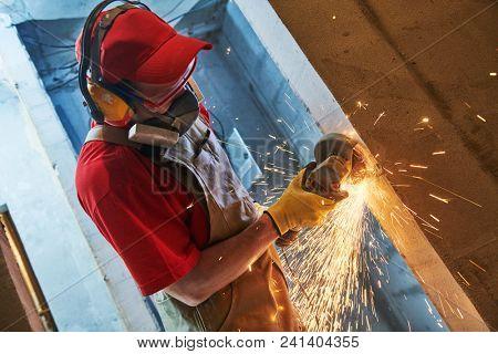home renovation. worker cutting metal reinforcement rods in doorway by grinder