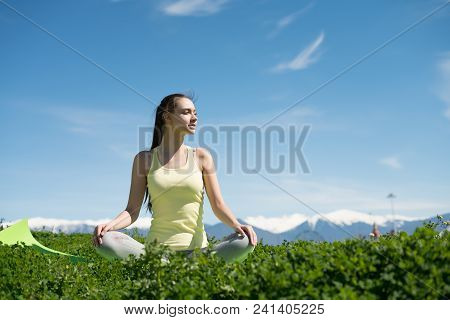 Peaceful Young Girl Meditates And Relaxes On The Green Grass In The Park, Doing Yoga