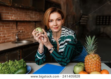 Beautiful Young Woman Holding Apple And Looking To Camera In Her Modern Loft Kitchen. Fitness Coach.
